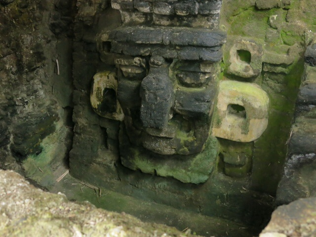 Carved face in the rock at Tikal