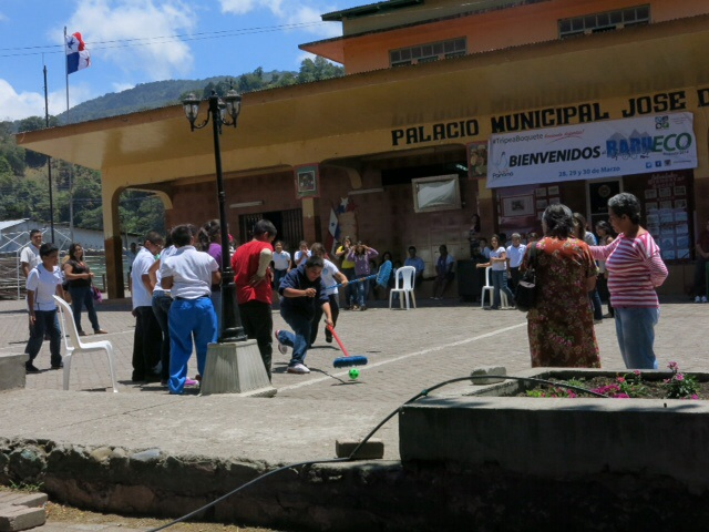 School children playing a game with brooms and a ball in the plaza