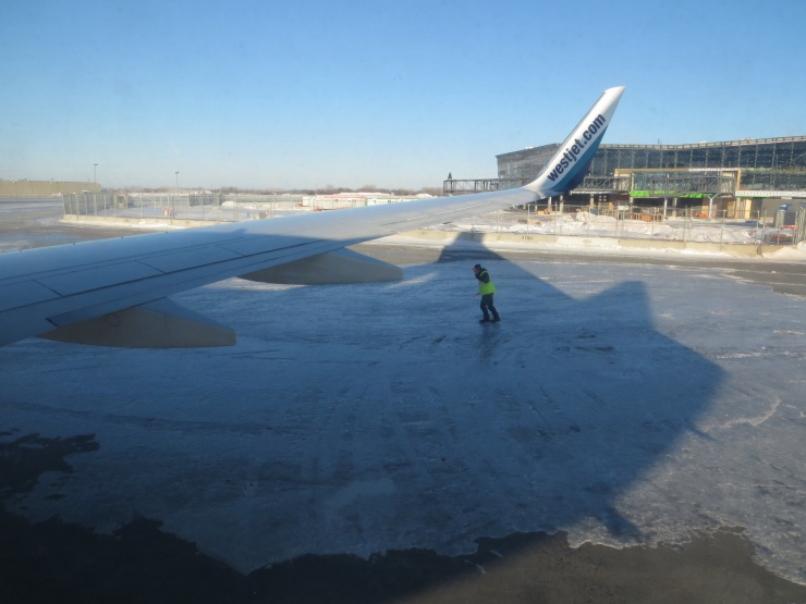 One of the airport workers sliding on the ice outside the plane