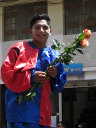 Boy on stilts giving away roses