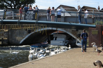 Boat disappearing under a very low bridge