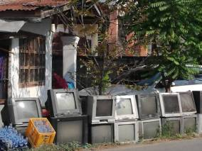 Row of old televisions outside a house